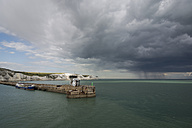 Great Britain, England, Dover, Cargo ship at harbour, White Cliffs and storm in the background - PAF001111
