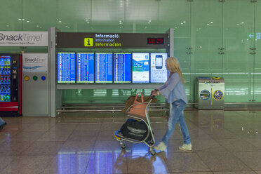 Spain, Canary Islands, Lanzarote, Arrecife, woman pushing baggage cart in front of display panel at airport - AM003543