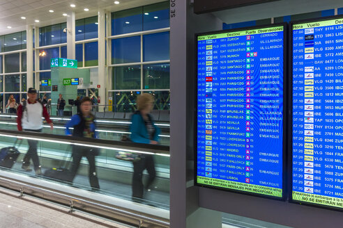 Spain, Canary Islands, Lanzarote, Arrecife, travellers and display panel at airport in the morning - AM003544