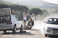 South Africa, Friends on a road trip stopping car for assistance with breakdown - ZEF002697