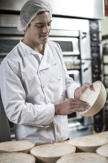 Baker preparing ceramic bowls for baking bread - ZEF003774