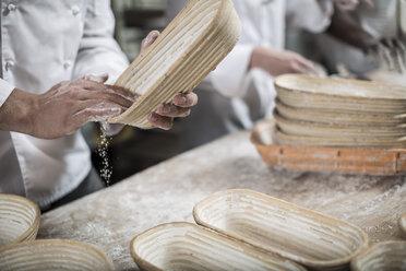Baker preparing ceramic bowls for baking bread - ZEF003779
