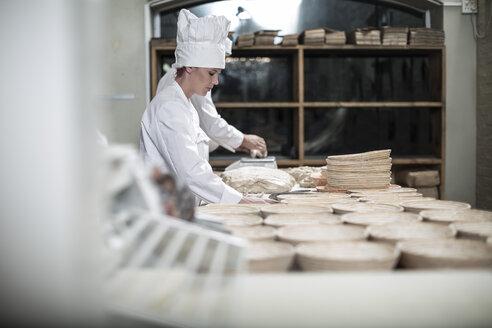 Female baker preparing ceramic bowls for baking bread - ZEF003784