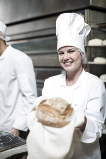 Female baker excited over baked bread fresh from the oven - ZEF003804