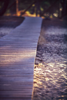 Spain, Andalusia, Huelva, wooden boardwalk through nature park at evening light - EH000050