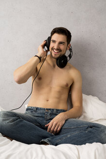 Shirtless man sitting on bed hearing music with headphones - SHKF000126