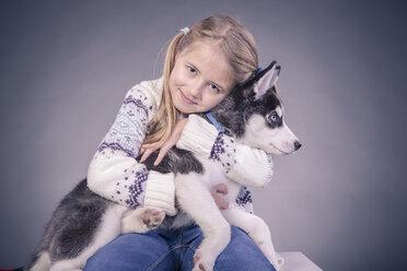 Blond girl holding husky puppy on lap - VT000387