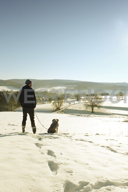 Germany, Bergisches Land, man walking dog in winter landscape - ONF000735