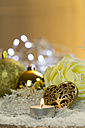 Christmas decoration with tea light, Christmas baubles and rose blossom on artifical snow - JUNF000164