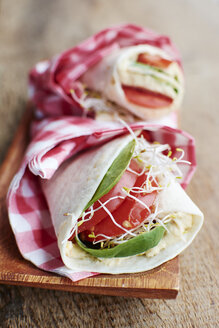 Tortilla wraps with humus, spinach leaves, sprouts and tomato slices on wooden board - HAWF000554