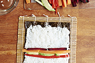 Making vegetable sushi with rice on a nori sheet - HAWF000564