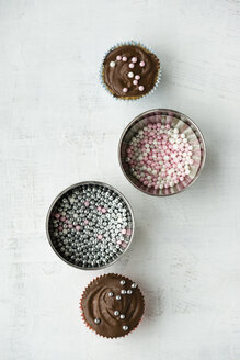 Two cupcakes with chocolate cream and sugar pearls and two bowls of sugar pearls - MYF000795