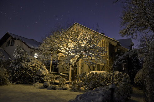 Germany, lighted one-family house with snow-covered garden in the foreground - KDF000527
