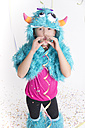 Girl masquerade as a monster standing in front of white background blowing streamer - YFF000291