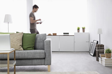 Young man using digital tablet in his living room - PDF000674
