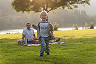 Happy boy running on meadow with family in background - PAF001200