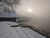 Germany, Kochel am See, snow-covered boathouse at shore of Lake Kochel - LAF001381