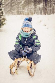 Germany, Bavaria, Berchtesgadener Land, happy boy on sledge - MJF001381