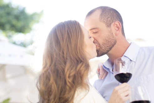 Couple holding wine glasses and kissing outdoors - ZEF003270