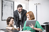 Businesswoman showing digital tablet to laughing colleagues - ZEF003040