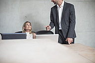 Businessman and businesswoman with laptop in conference room - ZEF003046