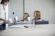 Three businesswomen drinking coffee in conference room - ZEF003047