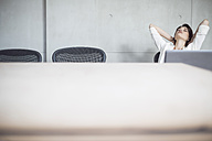 Businesswoman with laptop in conference room leaning back - ZEF003049