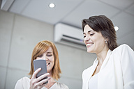 Two smiling businesswomen looking at cell phone - ZEF003057
