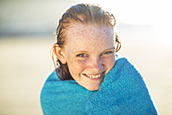 Portrait of smiling girl on the beach wrapped in a beach towel - ZEF003310