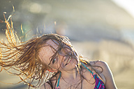 Girl on the beach smiling and swinging her hair in the wind - ZEF003314