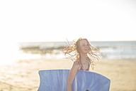Girl on the beach laughling and holding a boogie board - ZEF003317