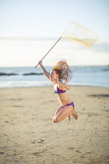 Happy girl on the beach jumping with a butterfly net - ZEF003320