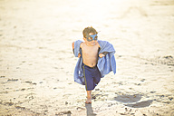 Little boy on the beach dressed up as a superhero with mask and towel - ZEF003412