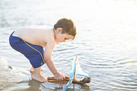 Boy on the beach playing with a toy wooden boat in the water - ZEF003415
