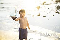 Boy on the beach presenting a toy wooden boat at the water - ZEF003417