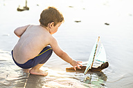 Boy on the beach playing with a toy wooden boat in the water - ZEF003420