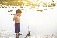 Boy playing with a toy wooden boat in the water - ZEF003421
