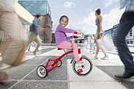 Girl riding a tricycle between a crowd of people in a city - ZEF003967