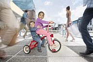 Girl and boy riding a tricycle between a crowd of people in a city - ZEF003968