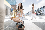 Saxophone player accepting a donation between a crowd of people in a city - ZEF003970
