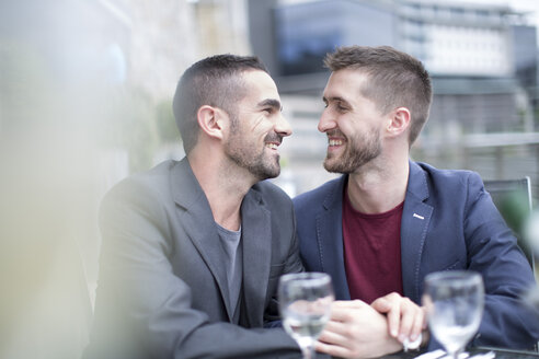 Gay couple sharing an intimate moment at a restaurant - ZEF002898