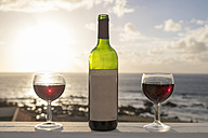 Spain, Canary Islands, La Gomera, two glasses of red wine and wine bottle - SIE006361