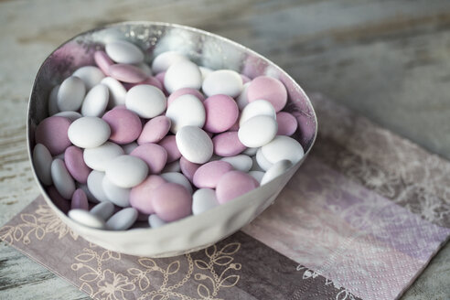 Bowl of white and pink chocolate beans on paper napkin - SARF001214