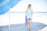 Girl on beach with flippers under sunshade - ZEF003327