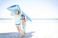 Two girls on beach carrying a lilo - ZEF003342