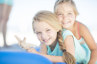 Two smiling girls on beach lying on a lilo with a starfish - ZEF003349