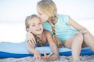 Two happy girls on beach on a lilo - ZEF003353