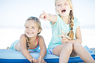 Two happy girls on beach on a lilo with starfish - ZEF003355