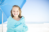 Smiling girl on beach wrapped in a towel - ZEF003364