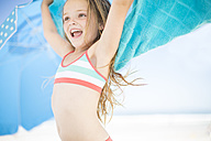 Smiling girl on beach drying off with a beach towel - ZEF003368